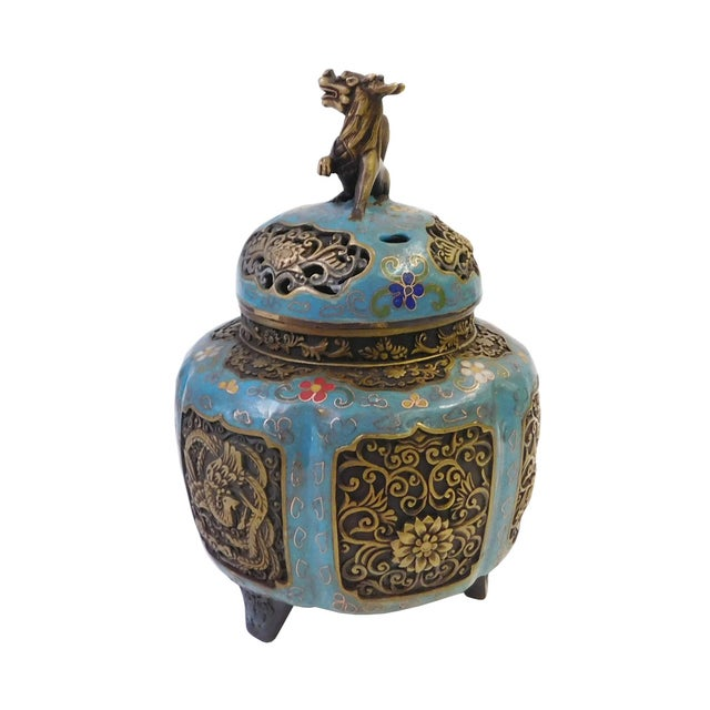 This is a round, tri legs incense ding burner made of metal and covered with blue enamel color. There are floral pattern...