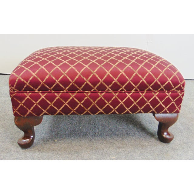 Queen Anne Style Upholstered Ottoman. Red upholstery with gold rope decoration with mahogany feet.