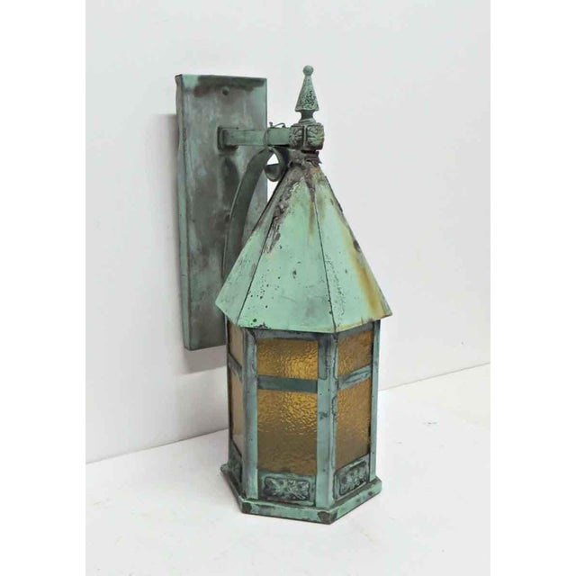 Copper lantern sconce with a verdigris patina and textured amber glass. Price includes wiring and cleaning.