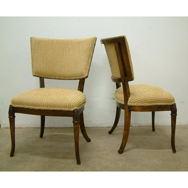 United States, circa 1930. An elegant pair of dark-stained beechwood Klismos chairs recovered in a cotton Thibaut fabric...
