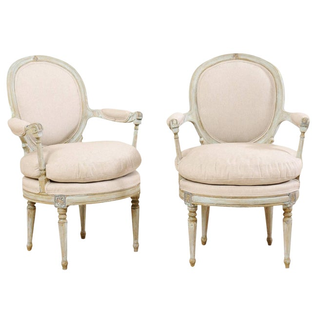 Pair of French Oval-Back Bergère Chairs With Delicately Carved Floral Motifs For Sale