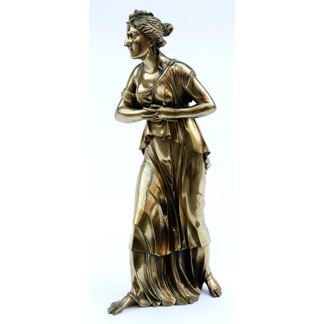 A masterful large classical statue in cast bronze of a beautiful young woman in stride wearing a flowing ionic chiton. The...