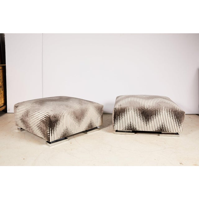 Vintage pair of midcentury square ottomans or poufs raised on platform feet of chrome and newly covered in Bargello...