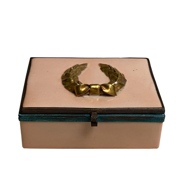 A salmon colored porcelain box with patina bronze surround and latch and topped with a gold laurel wreath.