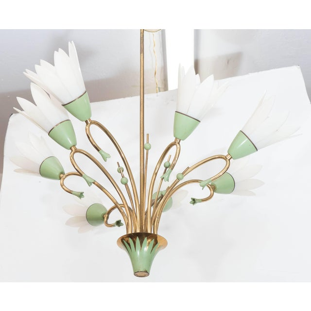 A whimsical circa 1960s chandelier, in brass with pale green enamel detail, with conical base, supporting curved stems and...