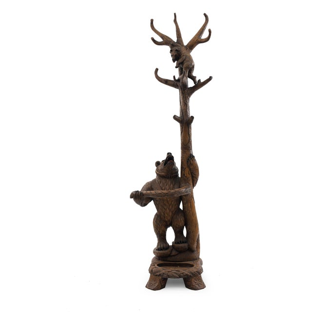 Rustic Black Forest style (20th century) walnut hatrack/umbrella stand with carved bears on base and one bear at top.