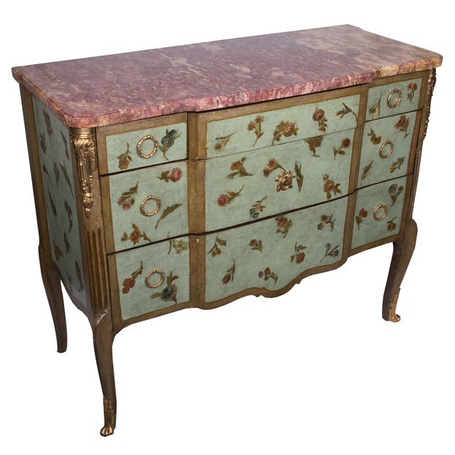 A softly decorated Louis XV/XVI transitional style commode, painted over-all with flowers on a light blue/green...
