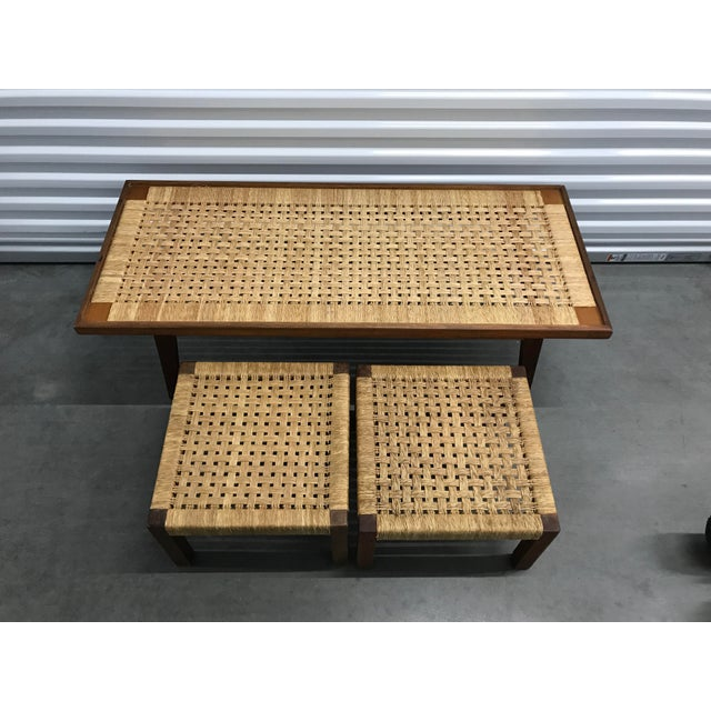 Vintage danish coffee table and stools with woven rope tops and wood frames. Two stools slide under coffee table for extra...