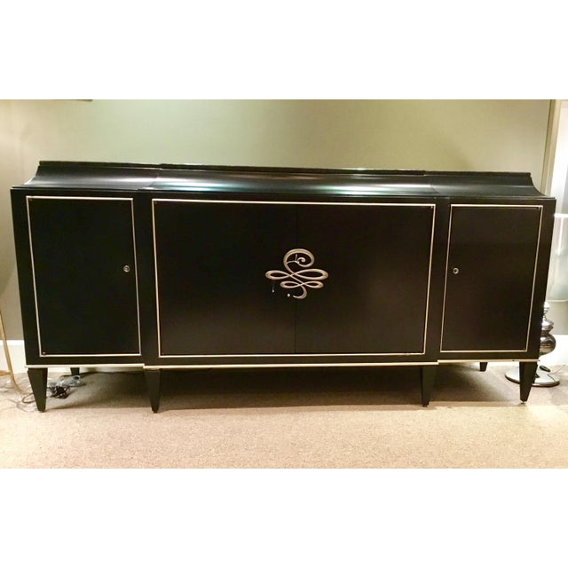 Elegant Caracole Rive Gauche Sideboard, with four doors, in an almost black finish depicting a natural wood, black granite...