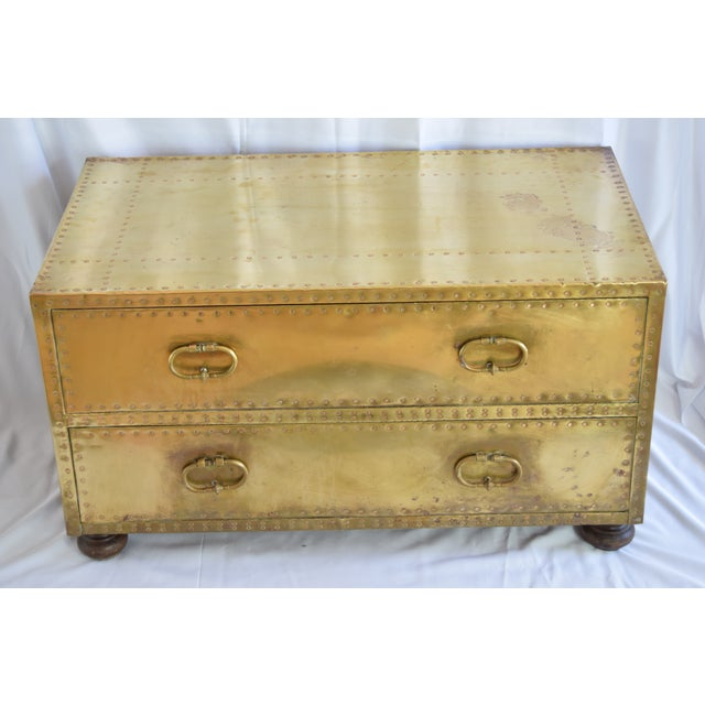 Brass two-drawer trunk with original lacquered finish and wood bun feet, circa 1970. Finished on all four sides. Sarreid...