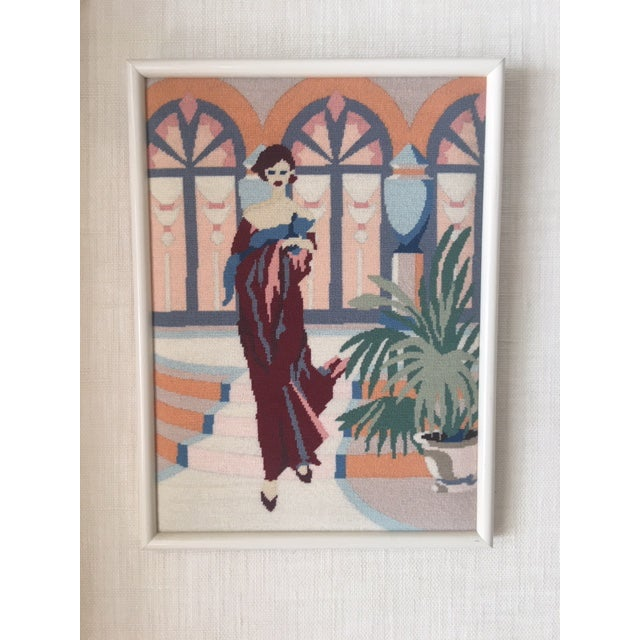 Art Deco style Needle point artwork. Depicts a lady in evening attire next to a potted palm in front of glassed doors....