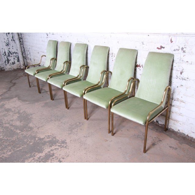 An exceptional set of six mid-century Hollywood Regency dining chairs by Mastercraft. The chairs feature sculpted brass...
