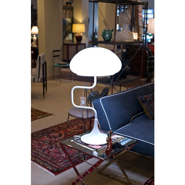 This vintage Mid-Century white lamp has a metal base with a plastic shade. The base is weighted and painted white, and the...