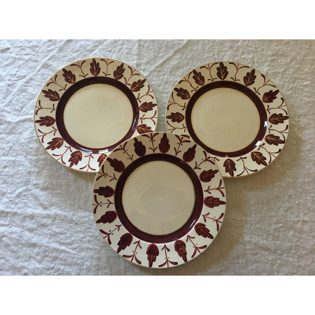 A wonderful trio of hand painted Midwinter English dinner plates with a 'Bloomsbury' vibe' each featuring quirky maroon...