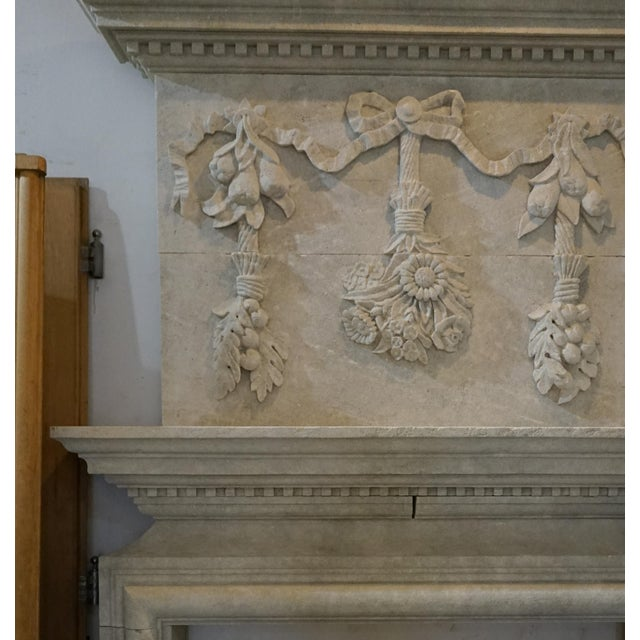 This lovely mantel was hand carved in France. Elegant floral, fruit and ribbon swag design carved on the trumeau....