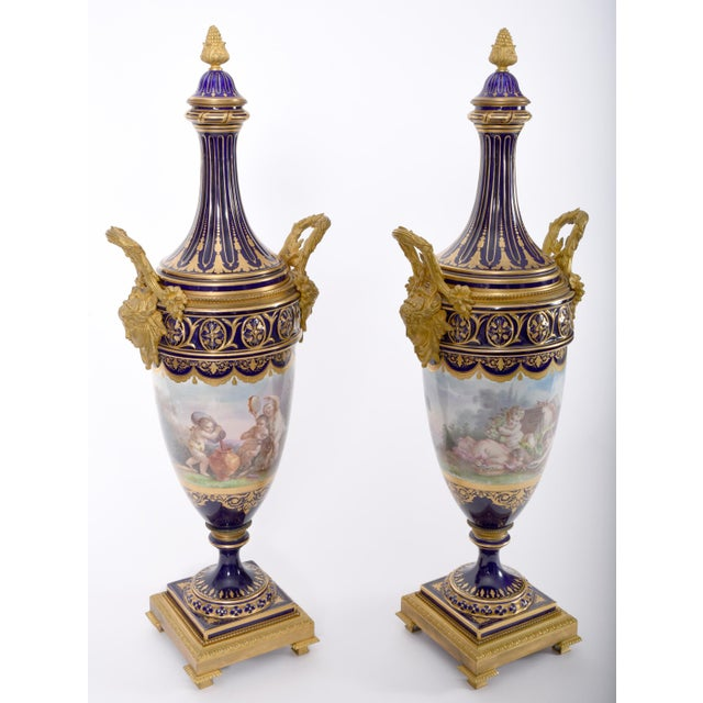 Early 19th century matching pair of Sèvres style gilt bronze mounted porcelain centerpiece urns. These superbly hand...