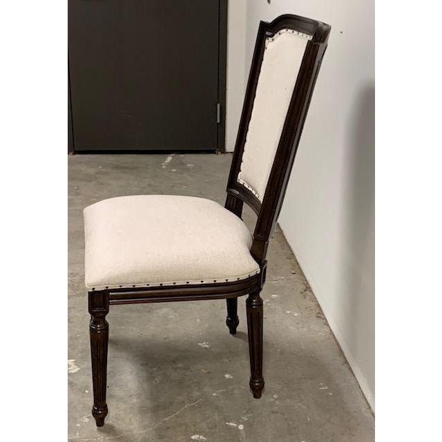 The woven accent chair form Universal is covered in a linen look fabric with a nail head tape. It has a has a carved frame...