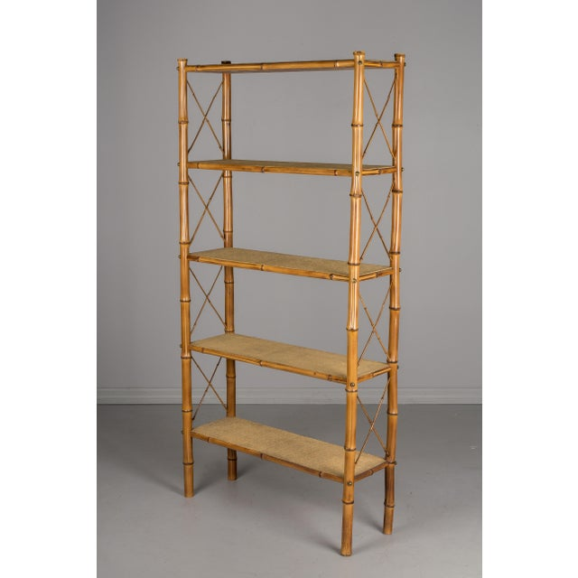 A Mid-Century Modern French etagere, or open bookcase, with a sturdy bamboo frame and tightly woven rattan shelves....