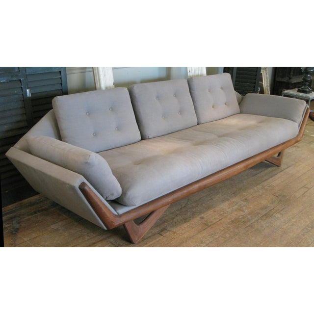 A Classic and beautiful 1950s three-seat gondola sofa designed by Adrian Pearsall for Craft Associates with walnut base....