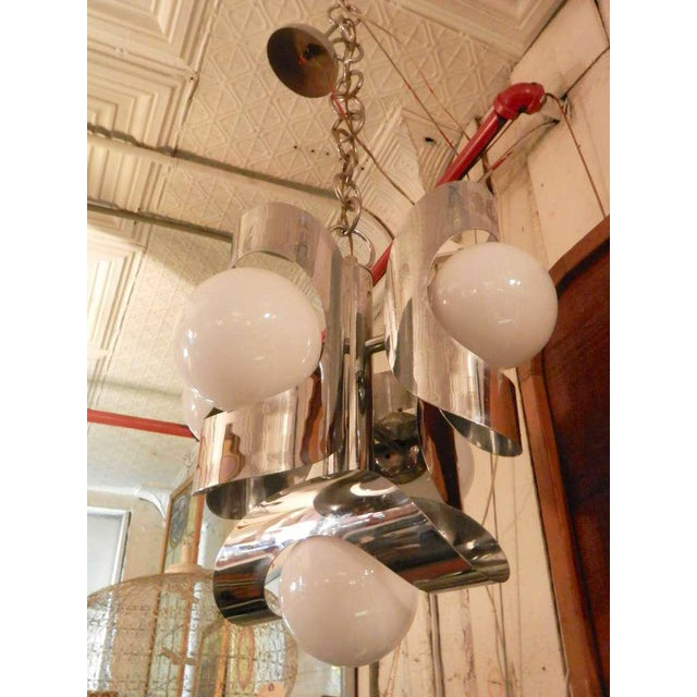 Mid-century five globe chandelier with surrounding bent chrome plates. The white globes give a soft glowing light, with...