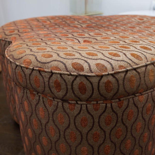 Trefoil ottoman in clean, vintage fabric of rust, burnt orange and brown colors.