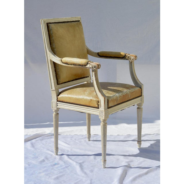 Wonderfully aged Louis XVI armchair in perfect eggshell paint and worn leather. The classic French armchair performs well...