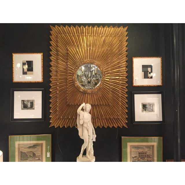 The show stealer mirror because of its monumental size and glitzy giltwood sunburst motif, having three layered rectangles...