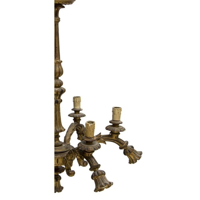 Louis XVI style gilt wood thirteen-light chandelier, Italy, early 20th c.. This chandelier features a central turned and...