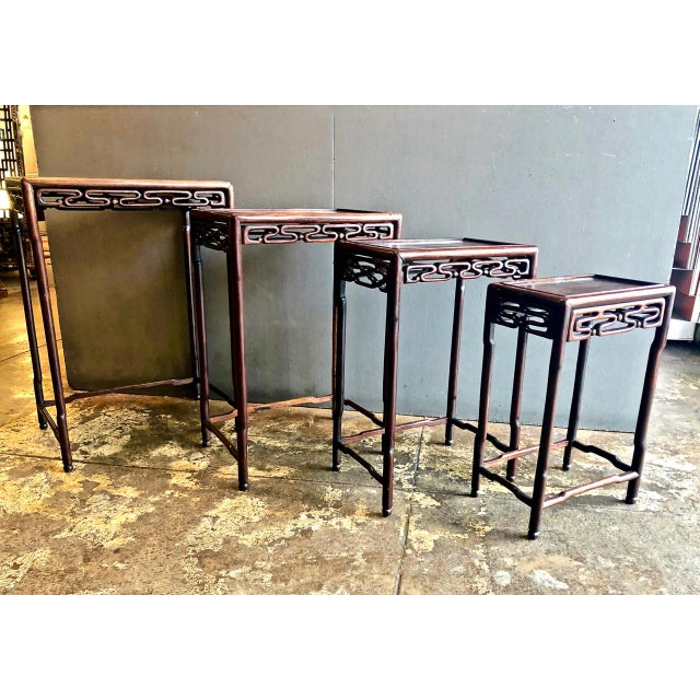 This is a good set of 4 Chinese carved rosewood nesting or quartteto tables that date to the late 19th or early 20th...
