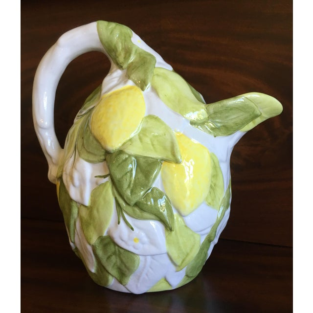 A whimsical lemon shaped pitcher from Italy embellished with raised yellow lemons, green and white leaves and white...