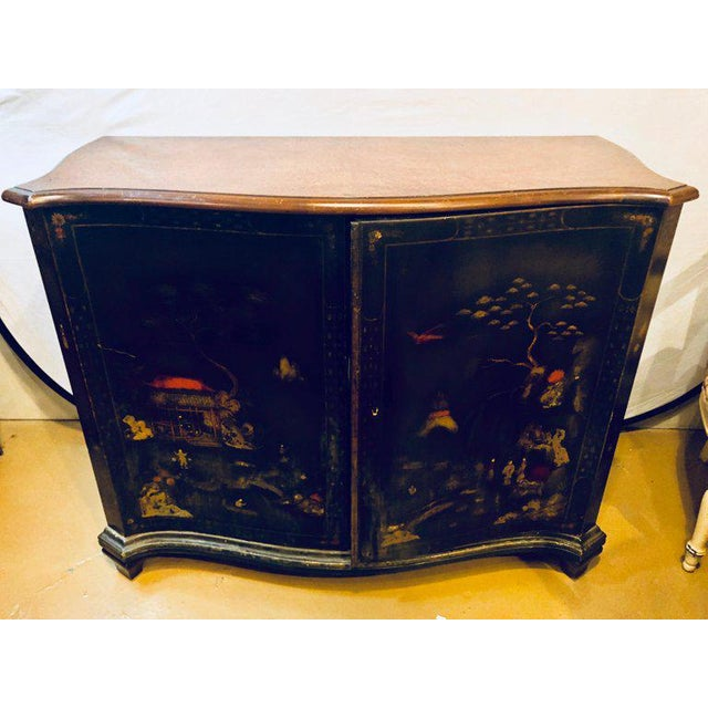 A fine custom quality Chinoiserie commode or cabinet server. The ebonized cabinet having two doors depicting a raised...