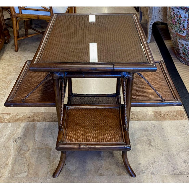 The side panels on this rattan and cane table become shelves. You give the bottom edge a tuh and pull it toward you. The...
