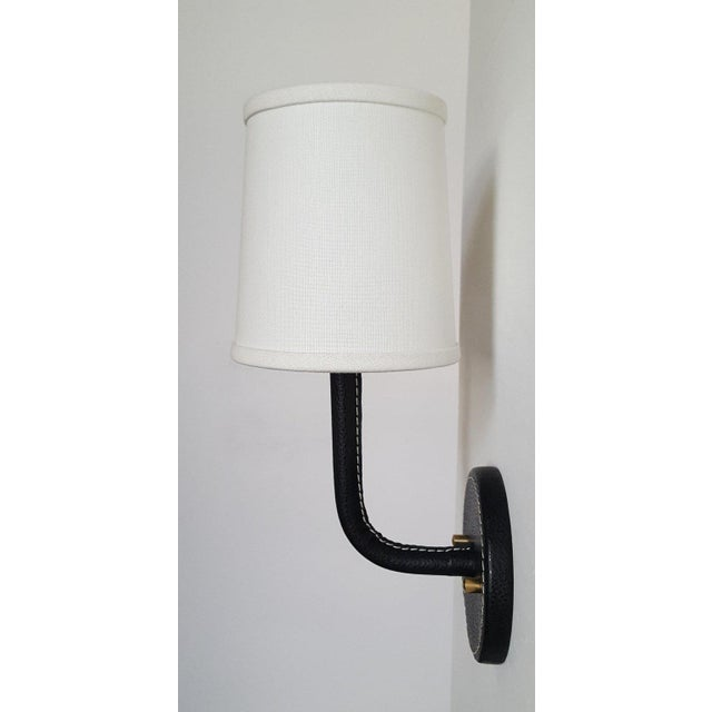 Paul Marra Leather Wrapped Adnet inspired wall sconce, shown in black, with top-stitched detailing. Top-stitching detail...