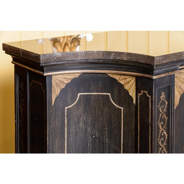 Impressive black and gold, marble top cabinet with painted decoration and concave ends which accentuate its beauty and...