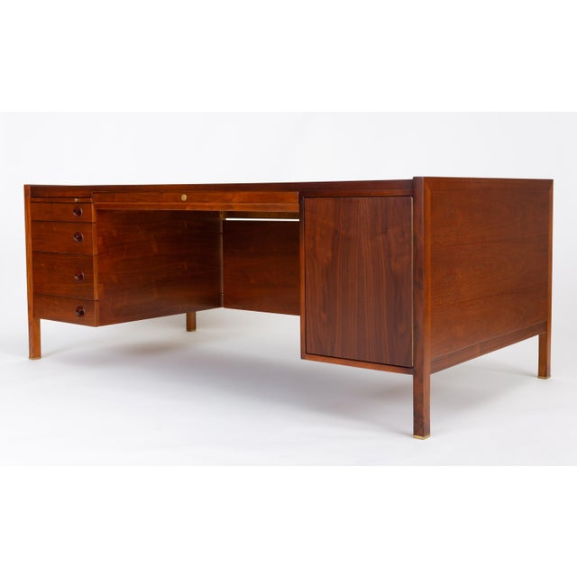 Edward Wormley's stately Model 807 executive desk for Dunbar Furniture in walnut, with rosewood and brass details. The...