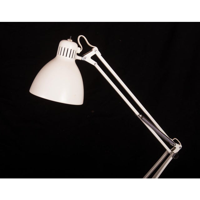 This lamp is attached to the side of a desk produced by Luxo in the 1980s. It is made of white lacquered steel and is in a...