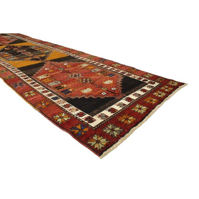 This vintage Turkish Oushak runner with Modern Tribal style features three hexagonal medallions with serrated edges in an...