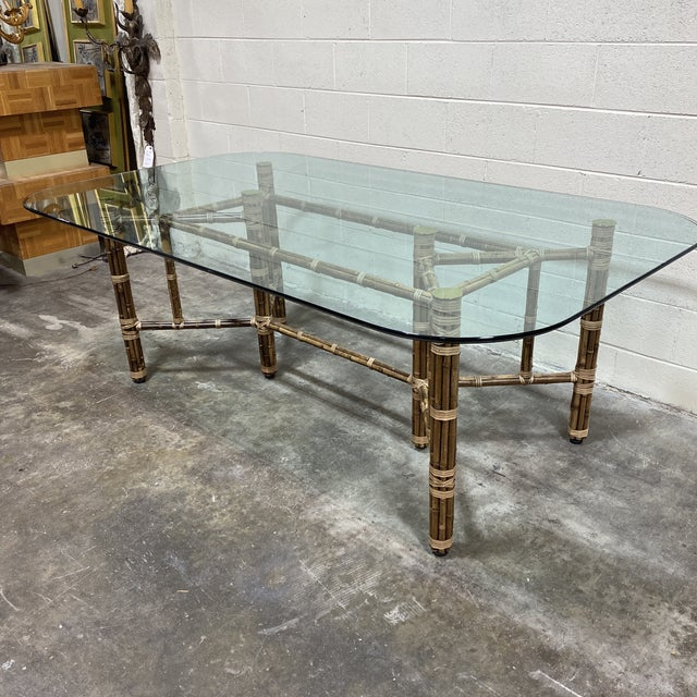 Rectangular glass top McGuire bamboo dining table with leather wrapped joints. Classic McGuire with style and durability....