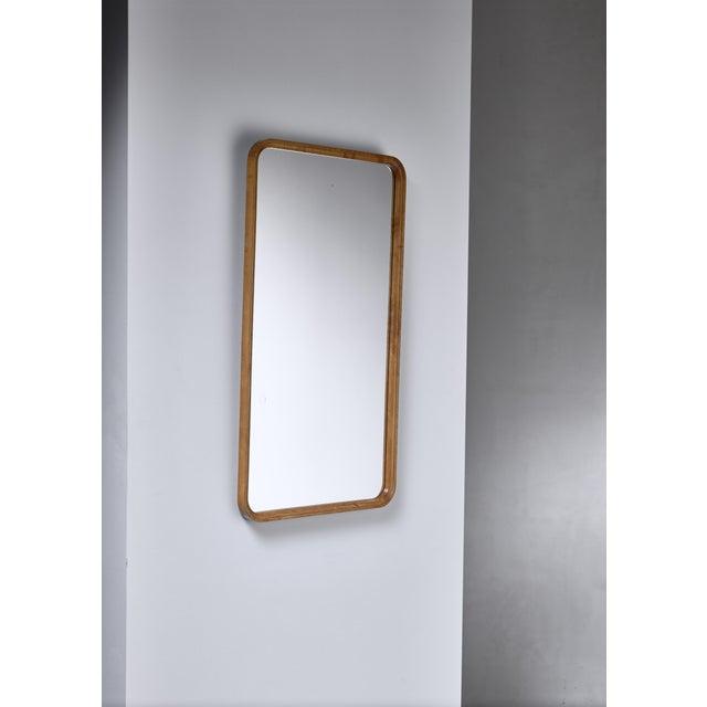 A Swedish rectangular wall mirror in an elegant birch wooden frame.