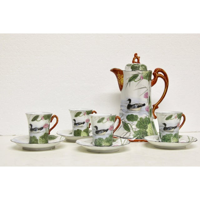 Handsome hand-painted Japanese porcelain chocolate set. Features one lidded teapot with four cups and saucers. Water lily...