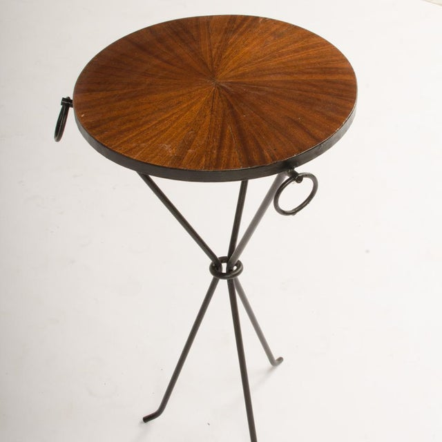 A pair of wrought iron drink tables with parquet tops and three iron rings. The tables rest on a sleek tripod form base....