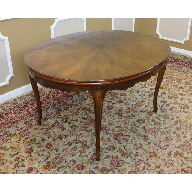 This is a very high quality fruitwood cherry French provincial style dining room table, unmarked but made by Baker...