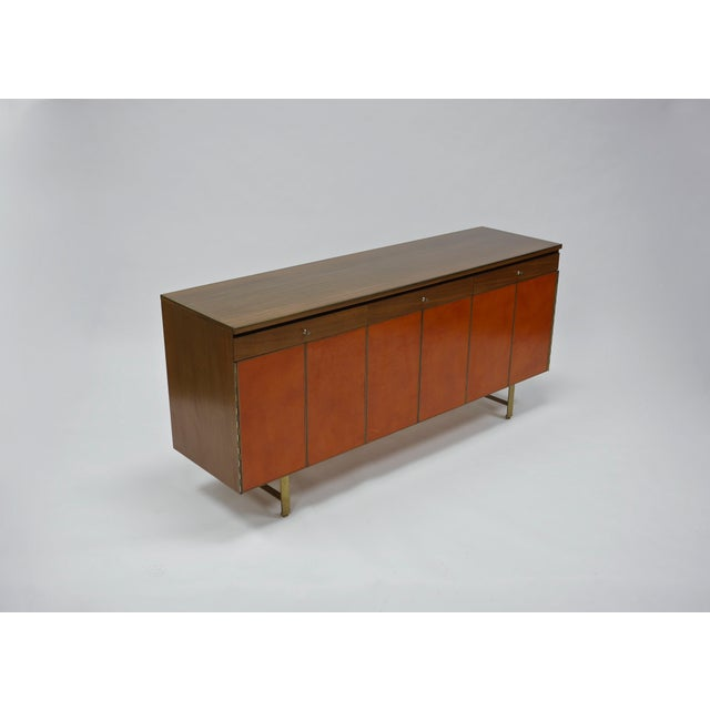 Rare and likely unique, Paul McCobb for Calvin Group walnut and leather front credenza with flat bar brass legs. Accordion...