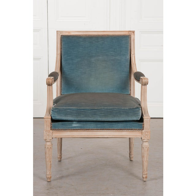 This elegant Louis XVI-style painted fauteuil, c. 1880, is from France and features a squared crest over padded open arms...