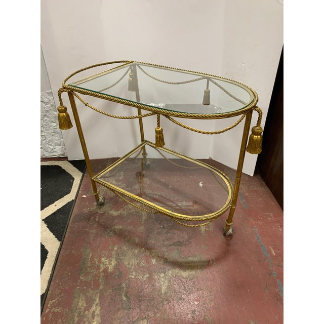 Oval demilune shape two-tier bar cart. Glass on each tier is surrounded by gilt metal rope and tassel trim. Three gilt...