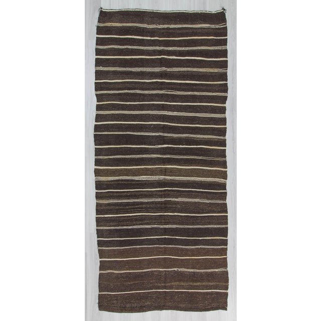 Natural striped kilim rug from Afyon region of Turkey. In very good condition. Colors include brown, black, and white....