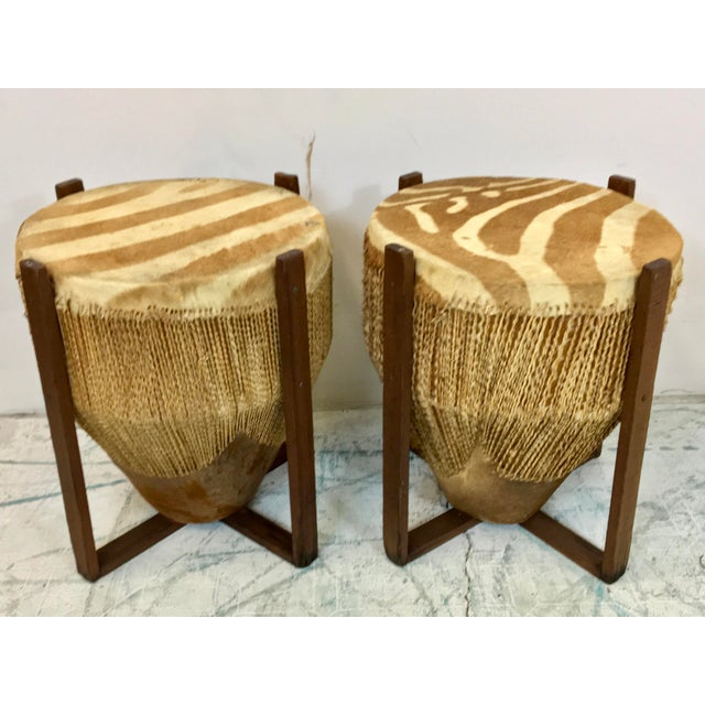 1950s African zebra skin drum tables. The drums are set in wood frames. There is notable age wear throughout the skin and...