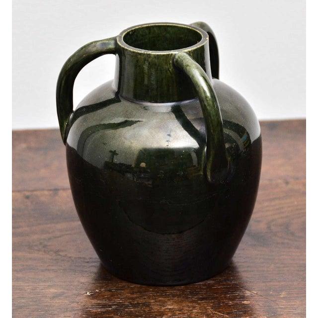 Dark green ceramic vase with high gloss glazing and three handles.