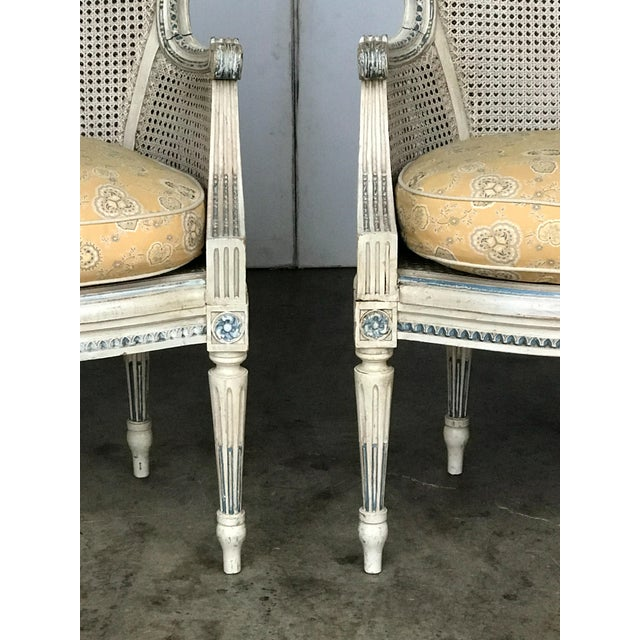 Pair of French late 19th century Louis XV style cream painted double caned bergeres. Finely carved and decorated....