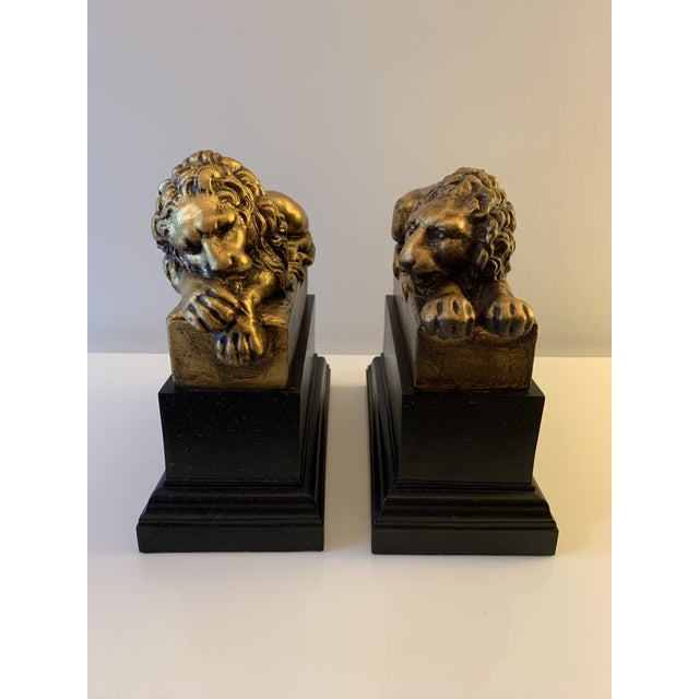 Gilt bookends, great detail in mane, one lion is awake while the other slumbers. Lions are resin material on wood base....